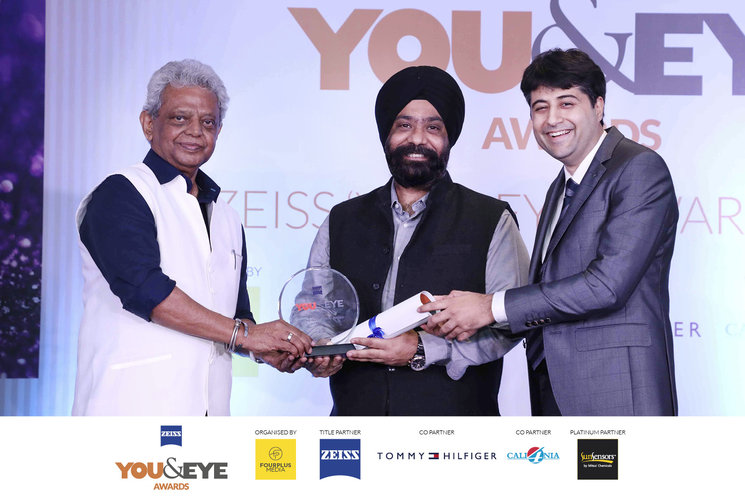 Jaspreet Singh, Titan Company Ltd accepting the award on behalf of Shree Ronnie Talati from Siraj Bolar, CEO, FourPlus Media and Rohan Paul, ZEISS